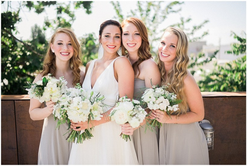 Bride with bridesmaids in light grey gowns holding white floral bouquets, Fremont Foundry wedding in Seattle, Wedding Planning and Design by Perfectly Posh Events, Seattle and Portland Wedding Planner, Photo by Alexandra Grace Photography