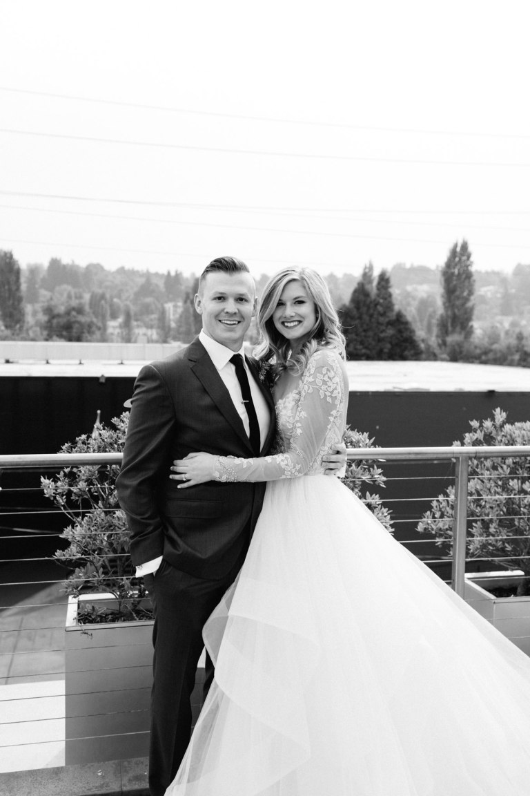Bride and groom pose together on rooftop with Seattle's Fremont neighborhood in background, black and white photograph, Fremont Foundry wedding, Seattle wedding, wedding planning and design by Perfectly Posh Events, Seattle Wedding Planner, Photo by Brittney Hyatt