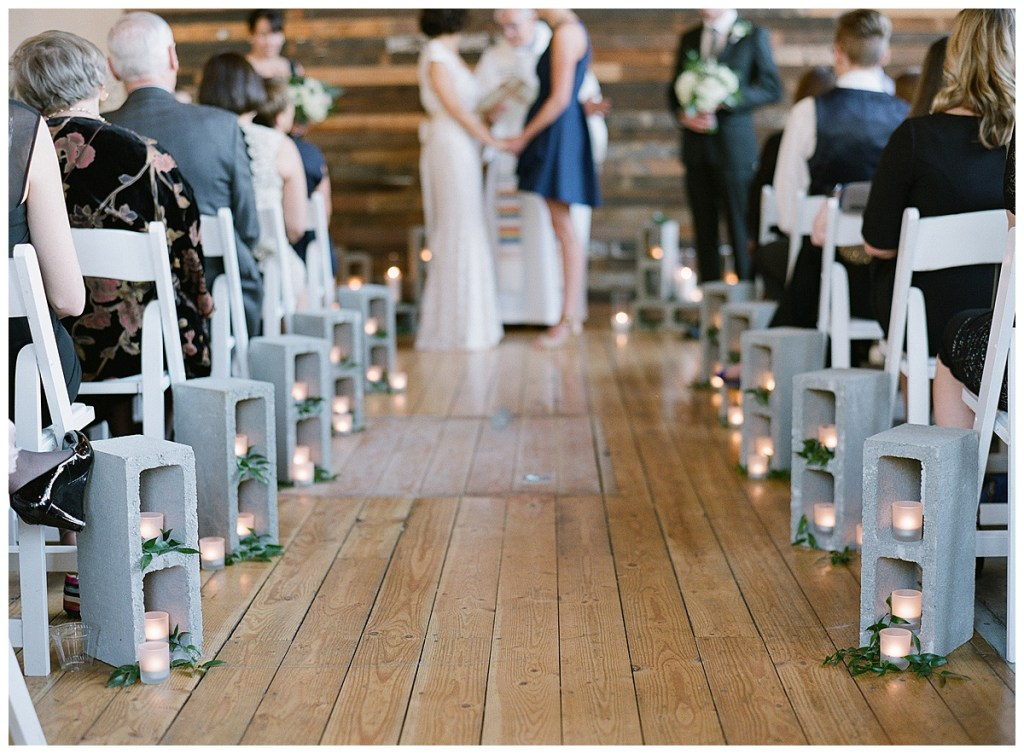 Same Sex Metropolist Wedding in Seattle, WA | Industrial modern wedding design, using cinder blocks down the aisle and at the altar with greenery and candles tucked in and around | Seattle Wedding Planner, Perfectly Posh Events | Katie Parra Photography | Floral Design by Sublime Stems