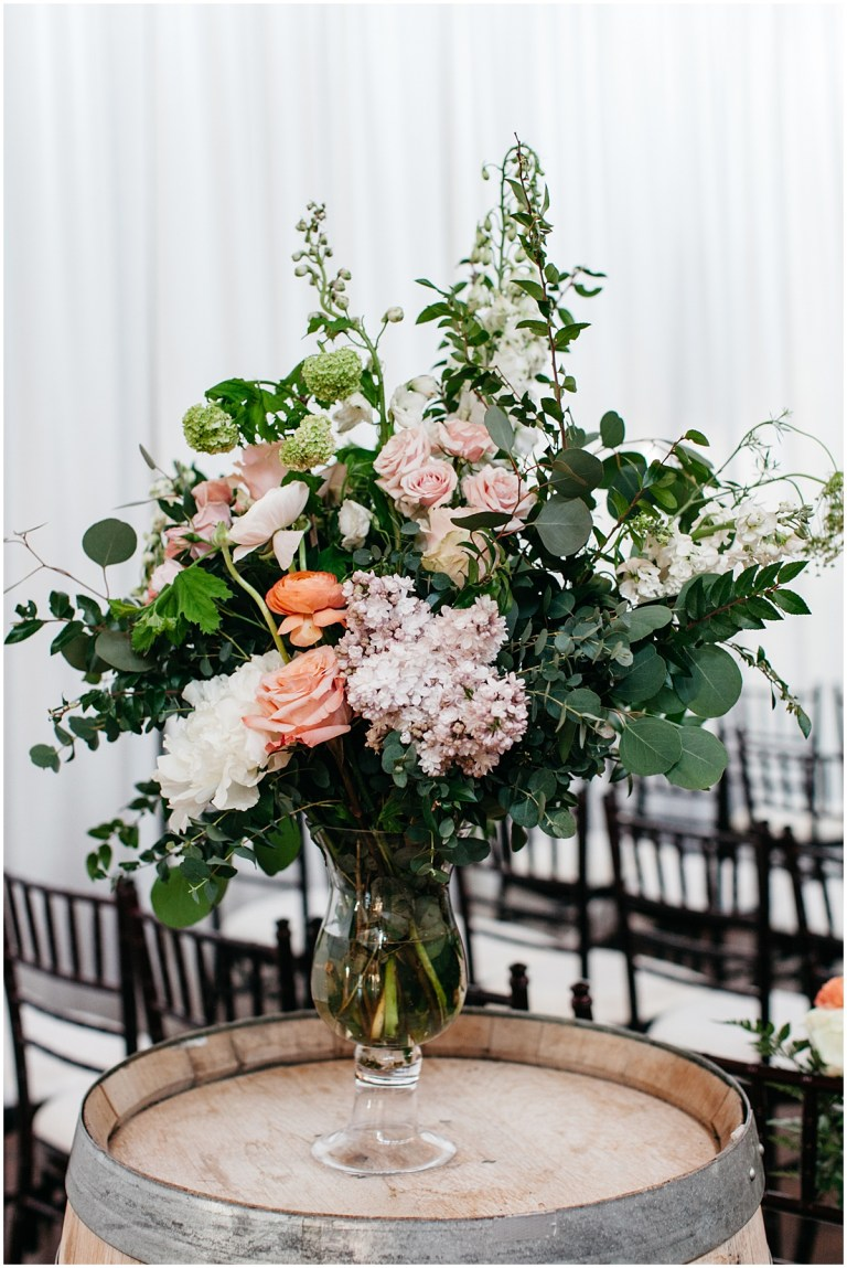 Large floral bouquet with white, blush, and coral flowers in a glass vase sits atop a wine barrel, Sodo Park wedding, Seattle wedding, Perfectly Posh Events wedding planning and design, Seattle and Portland Wedding Planner, Photo by Kate Price Photography