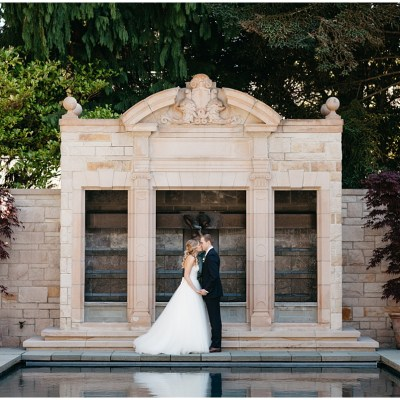 Bride and groom share a kiss while standing in front of arches with pool in foreground, Sodo Park wedding, Seattle wedding, Perfectly Posh Events wedding planning and design, Seattle and Portland Wedding Planner, Photo by Kate Price Photography
