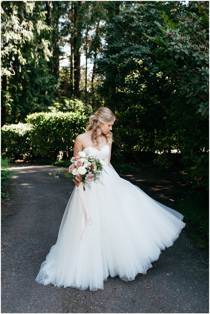 Bride in white wedding dress poses outside while holding large floral bouquet, Sodo Park wedding, Seattle wedding, Perfectly Posh Events wedding planning and design, Seattle and Portland Wedding Planner, Photo by Kate Price Photography