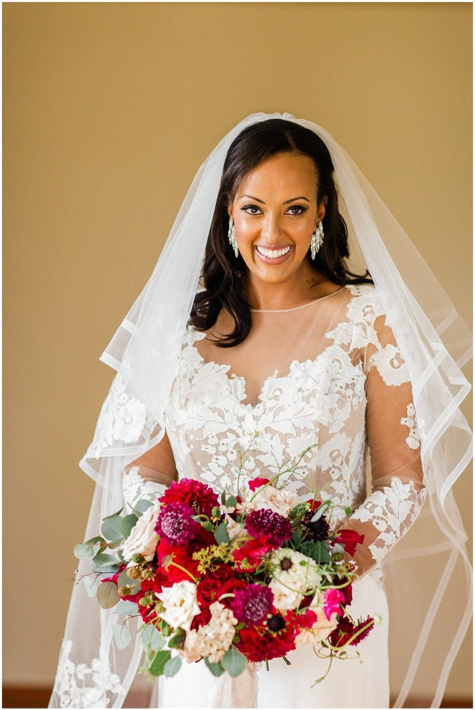 Bride in white lace gown with sleeves and a white veil poses while holding bouquet with ivory and burgundy flowers, Admiral