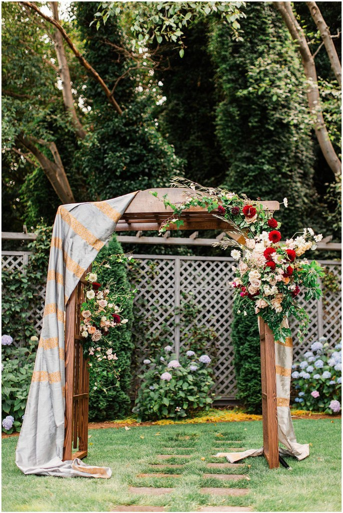 Wooden wedding altar decorated with greenery and blush, peach, and burgundy flowers and draped in silver and peach colored fabric, Admiral
