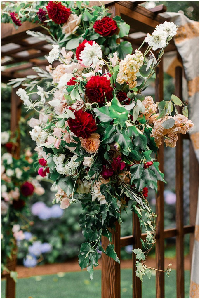 Details of wedding altar featuring greenery and blush, peach, and burgundy flowers, Admiral