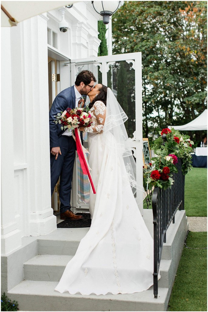 Bride and groom share a kiss outside of a classic white home, Admiral