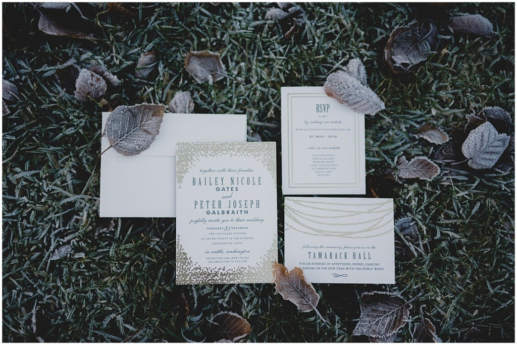 Custom designed wedding invitations arranged on grass covered in winter frost, New Years Eve wedding, Cedarbrook Lodge wedding, Seattle wedding, Perfectly Posh Events wedding planning, Washington wedding planner, Photo by Carly Bish