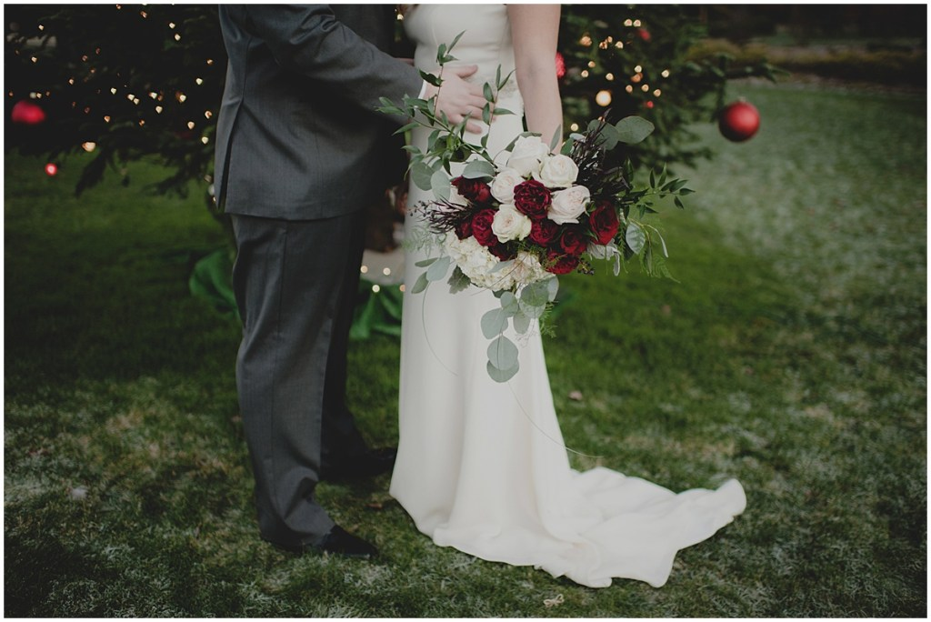 Bride and groom pose outside while the bride holds a bouquet made of ivory and deep red flowers, New Years Eve wedding, Cedarbrook Lodge wedding, Seattle wedding, Perfectly Posh Events wedding planning, Washington wedding planner, Photo by Carly Bish