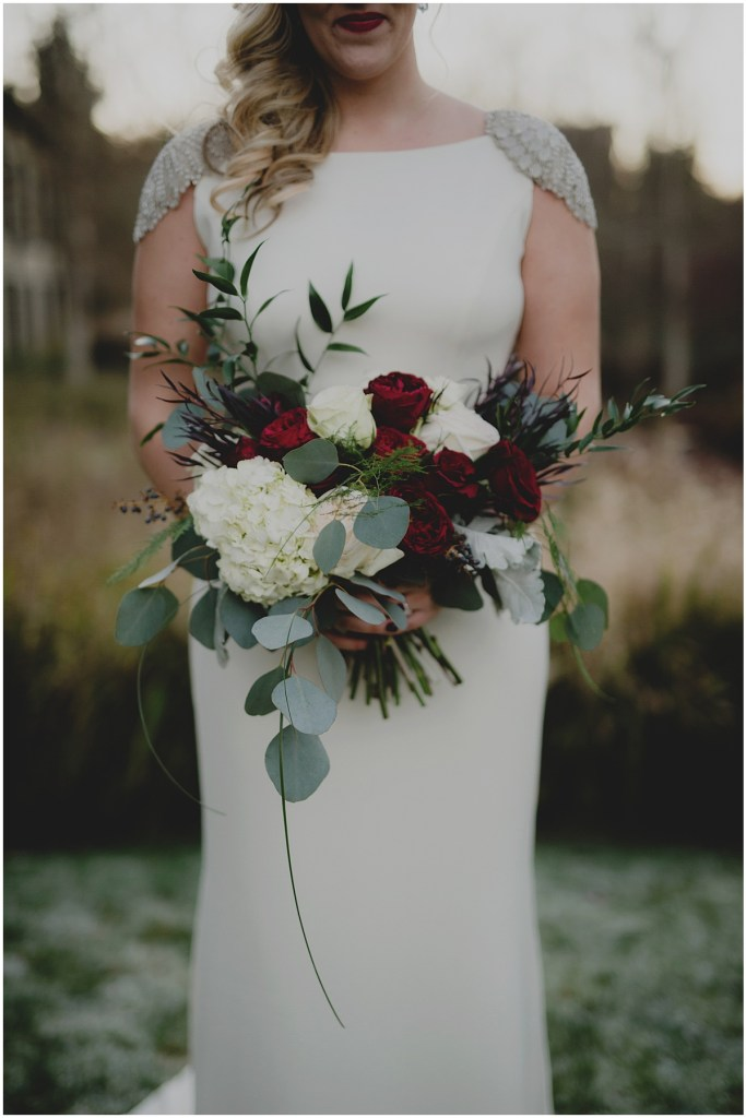 A bride poses outside while holding a bouquet made of ivory and deep red flowers, New Years Eve wedding, Cedarbrook Lodge wedding, Seattle wedding, Perfectly Posh Events wedding planning, Washington wedding planner, Photo by Carly Bish