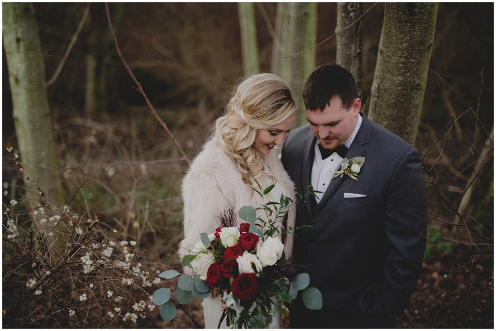 A bride poses with her groom while wearing a faux fur jacket over her white wedding gown and holding a bouquet made of ivory and deep red flowers, New Years Eve wedding, Cedarbrook Lodge wedding, Seattle wedding, Perfectly Posh Events wedding planning, Washington wedding planner, Photo by Carly Bish
