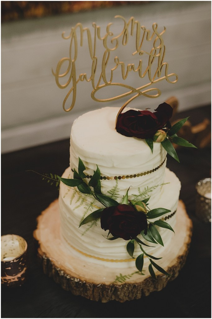 Two tier wedding cake with white frosting decorated with deep red flowers and greenery and topped with a custom gold sign, New Years Eve wedding, Cedarbrook Lodge wedding, Seattle wedding, Perfectly Posh Events wedding planning, Washington wedding planner, Photo by Carly Bish