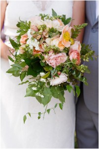 Close up of bride's floral bouquet with blush and coral flowers and pops of greenery, Kiana Lodge wedding, Perfectly Posh Events wedding planning, Seattle wedding planning, Photo by Amy Soper Photography
