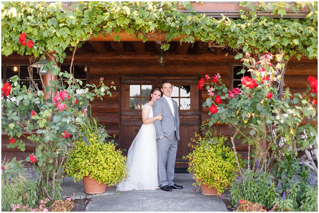 Bride and groom embrace while standing in front of lodge surrounded by floral bushes and vines, Kiana Lodge wedding, Perfectly Posh Events wedding planning, Seattle wedding planning, Photo by Amy Soper Photography