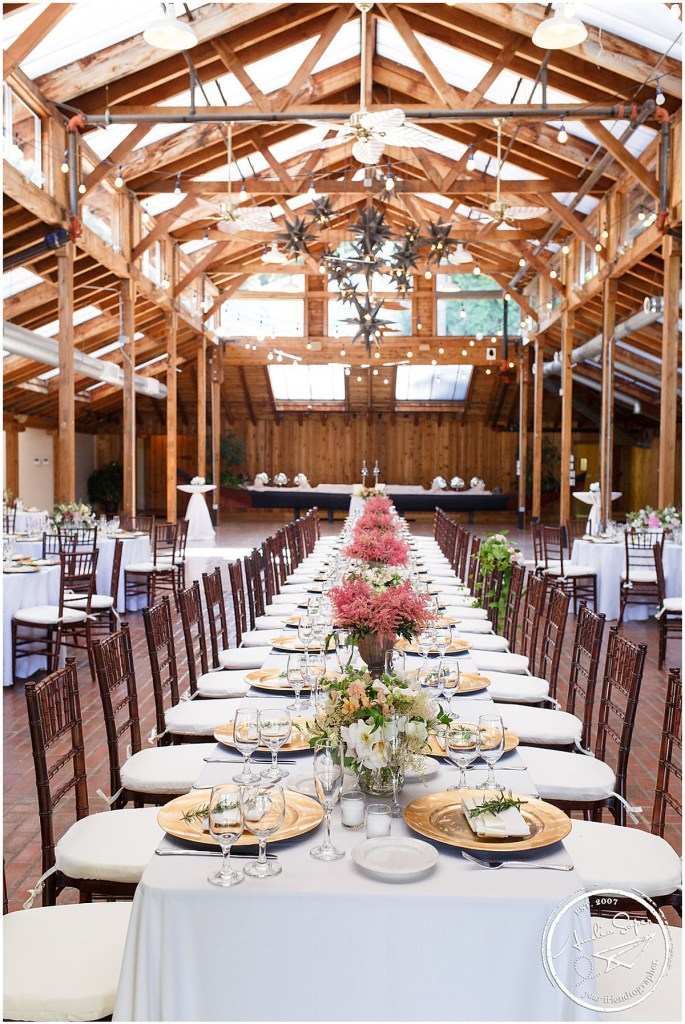 Long wedding reception table decorated with white table cloth and pink floral centerpieces inside lodge with a dramatic wood arch ceiling, Kiana Lodge wedding, Perfectly Posh Events wedding planning, Seattle wedding planning, Photo by Amy Soper Photography