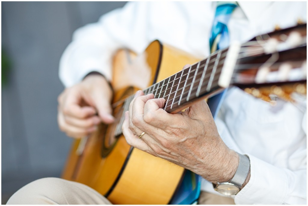 Close up of man playing an acoustic guitar at a wedding, Kiana Lodge wedding, Perfectly Posh Events wedding planning, Seattle wedding planning, Photo by Amy Soper Photography