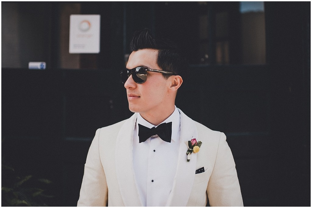 Groom in an ivory tuxedo and black sunglasses poses outside, mid century modern wedding, The Foundry by Herban Feast wedding, Seattle wedding, Perfectly Posh Events wedding planning and coordination, Photo by Carina Skrobecki