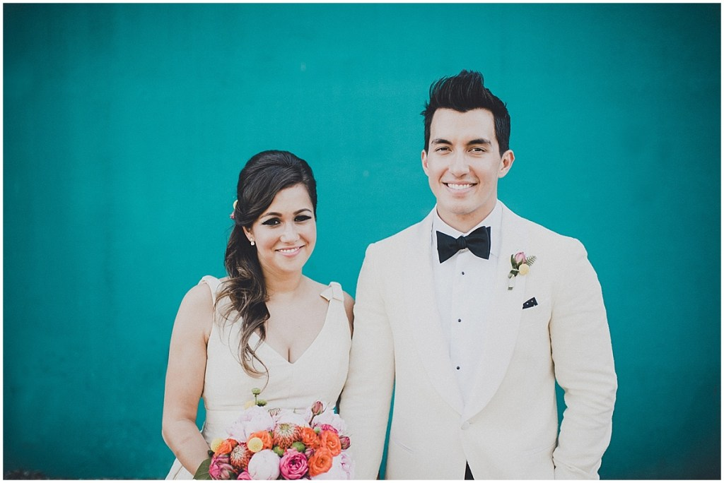 A bride holding coral, blush, and bright pink floral bouquet poses with her groom outside in front of teal blue wall, mid century modern wedding, The Foundry by Herban Feast wedding, Seattle wedding, Perfectly Posh Events wedding planning and coordination, Photo by Carina Skrobecki