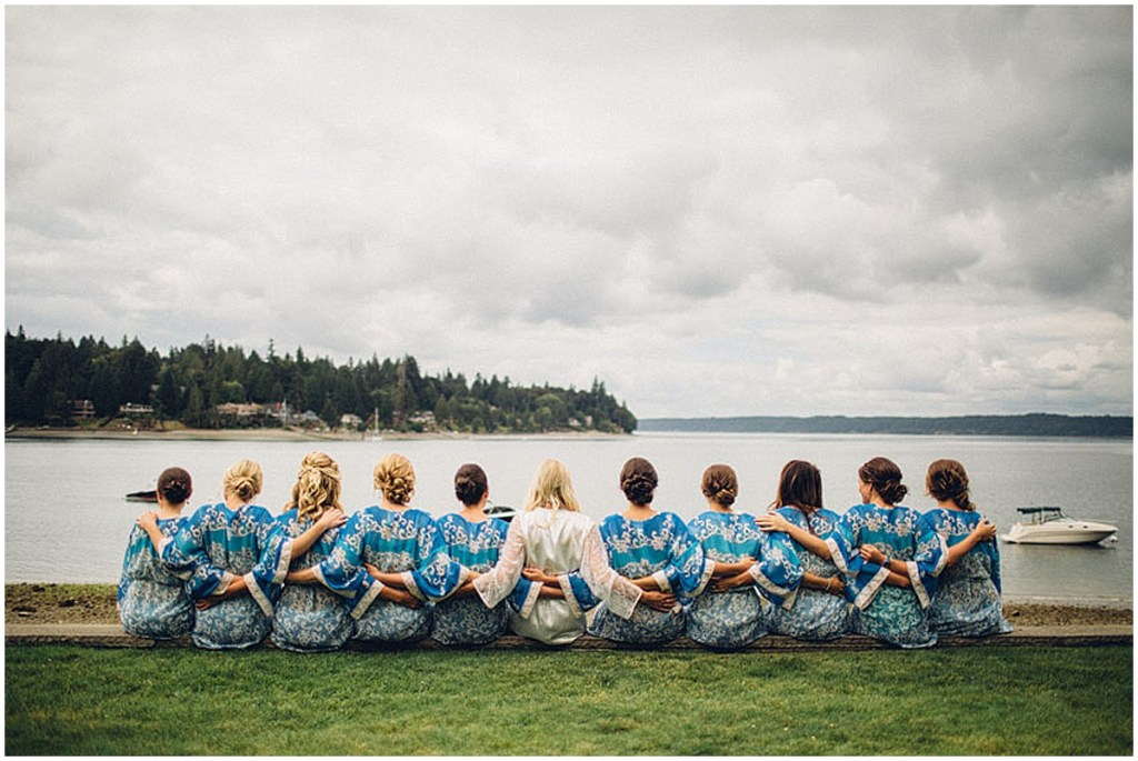 The backs of a bride and her bridesmaids posing in white and blue robes in front of the waters of Puget Sound, Washington wedding, Perfectly Posh Events wedding planning, Washington wedding planning and coordination, Photo by Mike Fiechtner Photography