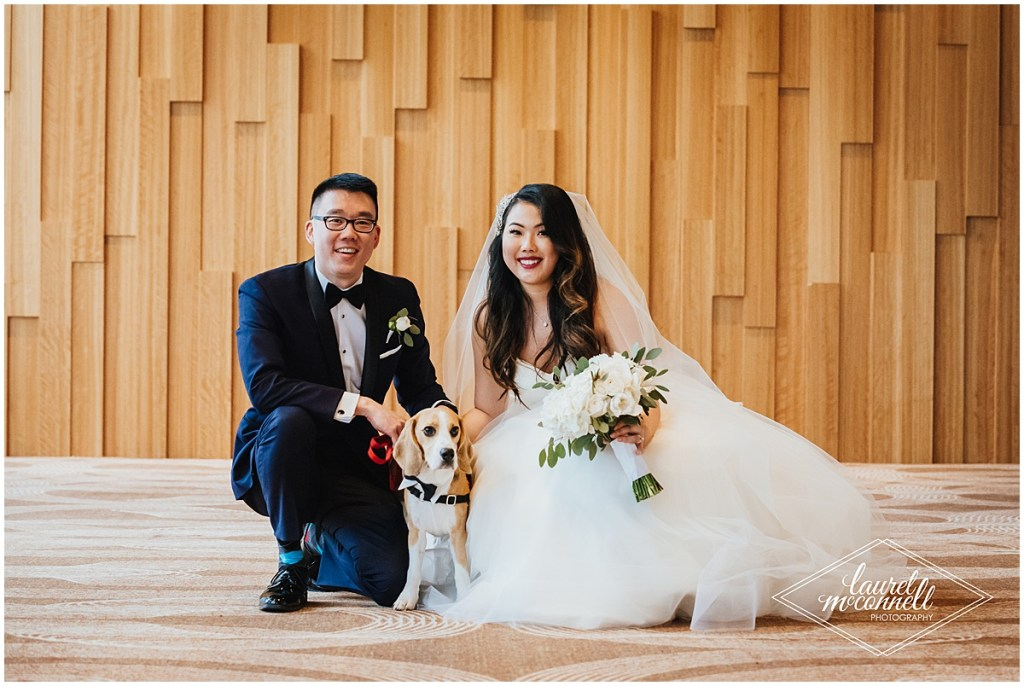 Bride and groom pose indoors in front of wood paneled wall with their pet beagle dog, The Foundry by Herban Feast wedding, Seattle wedding, wedding planning by Perfectly Posh Events, Photo by Laurel McConnell Photography