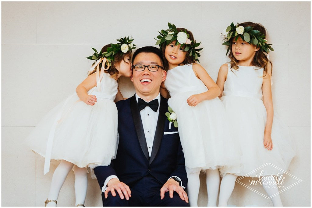 Groom smiles with three flower girls in white dresses and floral and greenery crowns, The Foundry by Herban Feast wedding, Seattle wedding, wedding planning by Perfectly Posh Events, Photo by Laurel McConnell Photography