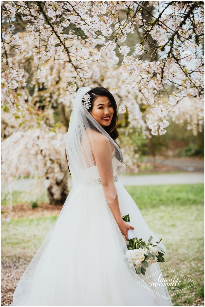Bride in an off white wedding gown and long sheer veil poses under a tree covered in cherry blossoms, The Foundry by Herban Feast wedding, Seattle wedding, wedding planning by Perfectly Posh Events, Photo by Laurel McConnell Photography
