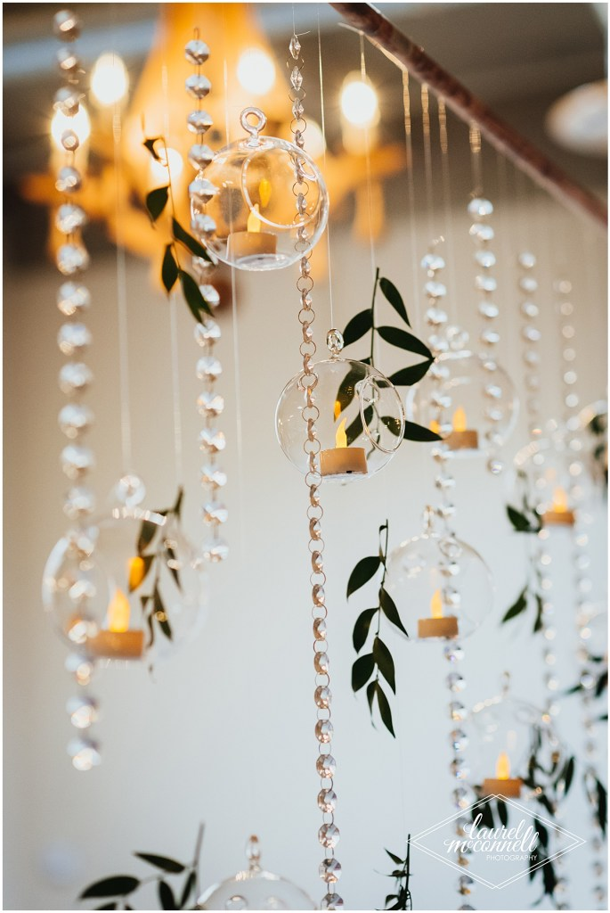 Crystal garlands and greenery hang from the ceiling alongside faux tea light candles in glass spheres, The Foundry by Herban Feast wedding, Seattle wedding, wedding planning by Perfectly Posh Events, Photo by Laurel McConnell Photography