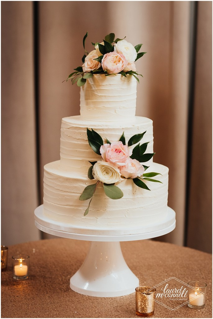 Three tier wedding cake covered in white buttercream frosting and decorated with blush and ivory flowers, The Foundry by Herban Feast wedding, Seattle wedding, wedding planning by Perfectly Posh Events, Photo by Laurel McConnell Photography