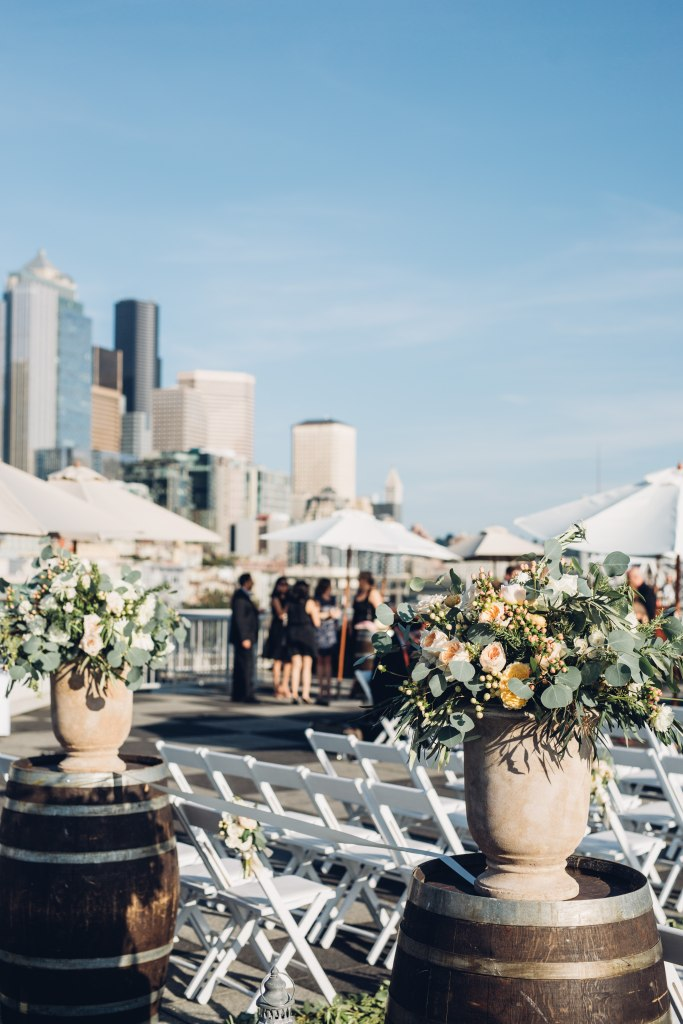 Two urns filled with large greenery and coral flower bouquets sit on top of wine barrels at a rooftop wedding ceremony, Italian inspired wedding, Bell Harbor at Pier 66 wedding, Seattle wedding, planning by Perfectly Posh Events, Seattle wedding planner, Photo by Mike Fiechtner Photography