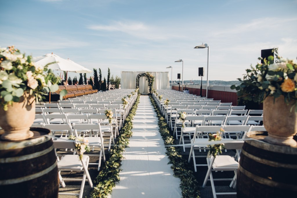 A wedding ceremony is set up on a rooftop by Seattle