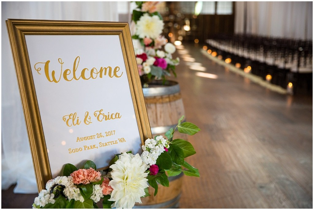 A custom made wedding welcome sign in a large gold frame accessorized with ivory and pink flowers with touches of greenery, Sodo Park wedding, Seattle wedding planner, Perfectly Posh Events, Photo by La Vie Photography