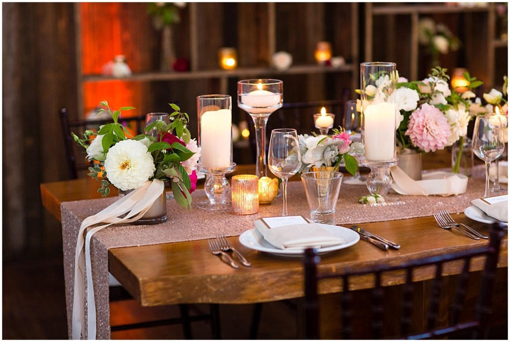A long wood wedding reception dinner table decorated with a gold table runner, white pillar candles and ivory, blush, and red floral centerpieces, Sodo Park wedding, Seattle wedding planner, Perfectly Posh Events, Photo by La Vie Photography