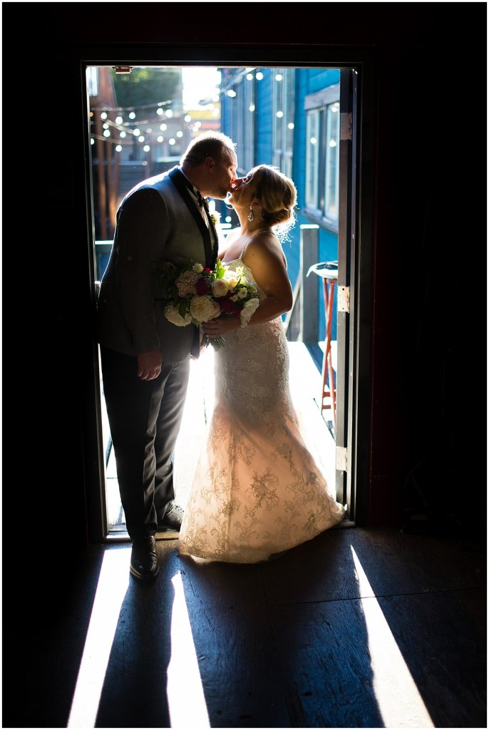 Bride and groom share a kiss while standing in a doorway, Sodo Park wedding, Seattle wedding planner, Perfectly Posh Events, Photo by La Vie Photography