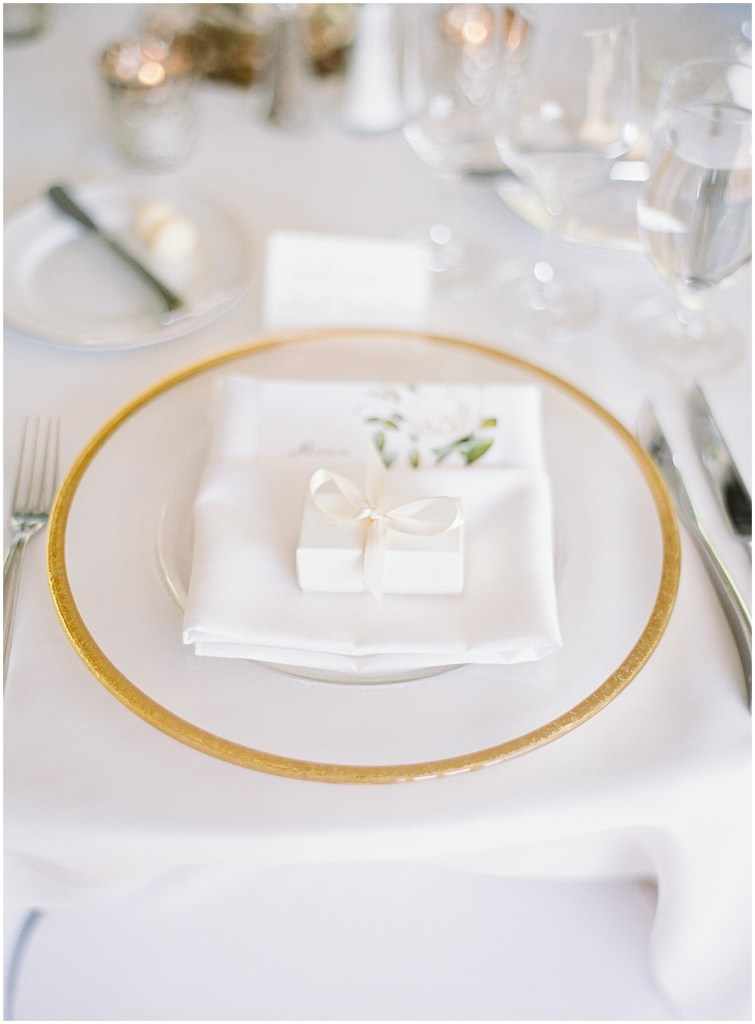 Wedding table setting featuring a white plate with gold etching, white napkins, and a small gift in a white box, DeLille Cellars wedding, Woodinville wedding, Perfectly Posh Events wedding coordination, Photo by Great Romance Photography