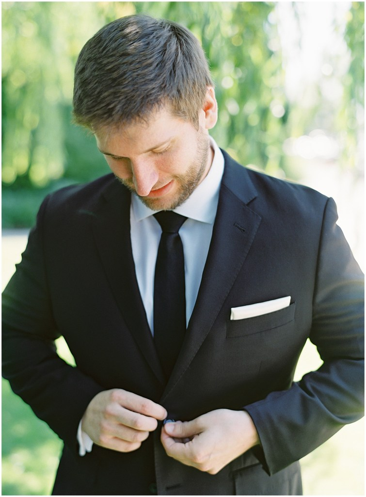 Groom poses outside while buttoning his tuxedo, DeLille Cellars wedding, Woodinville wedding, Perfectly Posh Events wedding coordination, Photo by Great Romance Photography