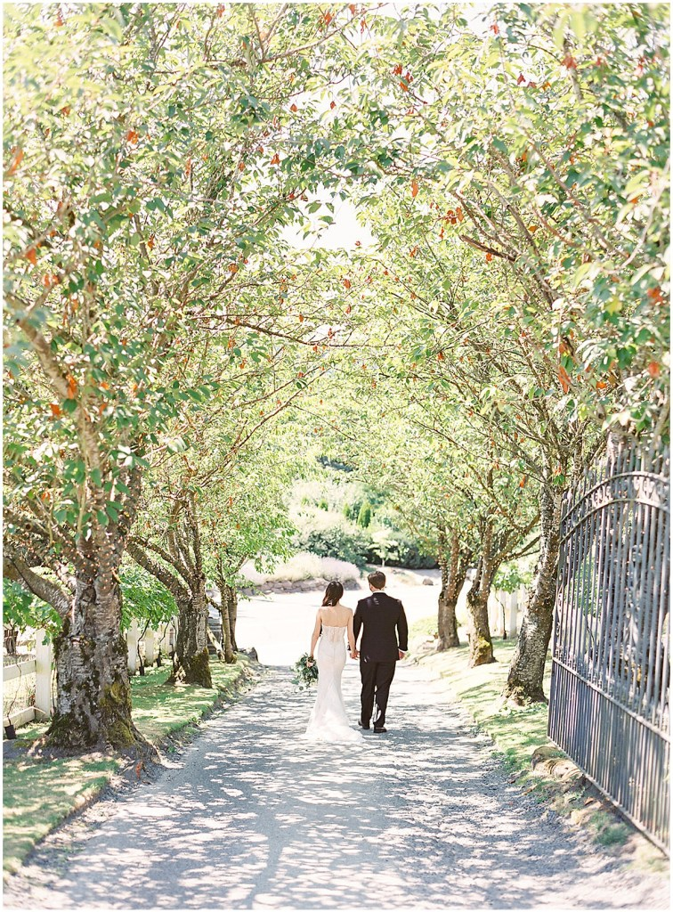 Bride and groom walk down a pathway lined with blooming trees, Chateau Lill wedding, Woodinville wedding, Perfectly Posh Events wedding coordination, Photo by Great Romance Photography