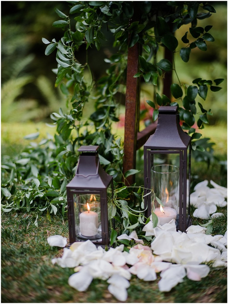 Close up of wedding ceremony decorations with white pillar candles in rustic iron lanterns accessorized with white rose petals, DeLille Cellars wedding, Washington wedding planner, Perfectly Posh Events, Photo by Shane Macomber Photography