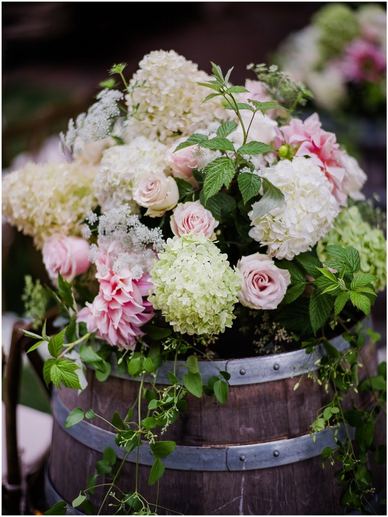 Large floral vase with ivory hydrangeas and pink roses sitting atop a wine barrel, DeLille Cellars wedding, Washington wedding planner, Perfectly Posh Events, Photo by Shane Macomber Photography