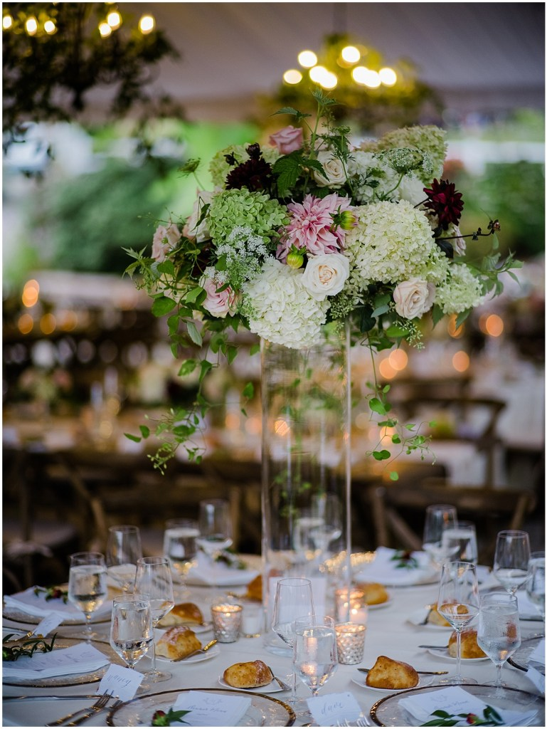 Wedding reception dinner table featuring a centerpiece with pink, ivory, and blush, flowers in an extra tall glass vase, DeLille Cellars wedding, Washington wedding planner, Perfectly Posh Events, Photo by Shane Macomber Photography