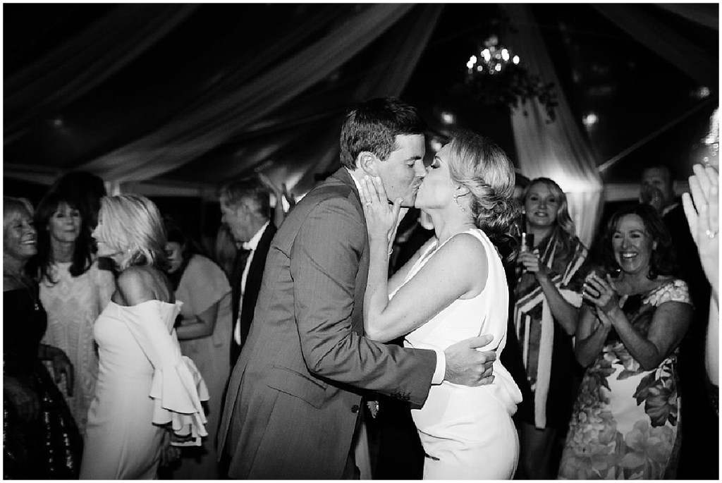 Black and white photo of bride and groom sharing a kiss while dancing at their wedding reception, PNW outdoor summer wedding, Washington wedding designer, Perfectly Posh Events, Photo by Kate Price Photography
