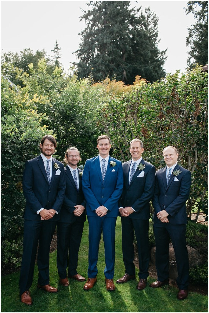 Groom in a blue suit poses with his groomsmen outside in front of green bushes, PNW outdoor summer wedding, Washington wedding designer, Perfectly Posh Events, Photo by Kate Price Photography