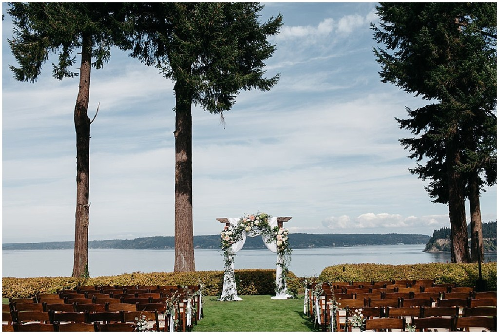 Outdoor wedding ceremony with a view of Puget Sound in the background set up with rustic wood chairs and a wood altar covered in ivory and pink flowers with greenery and draped in a white cloth, PNW outdoor summer wedding, Washington wedding designer, Perfectly Posh Events, Photo by Kate Price Photography