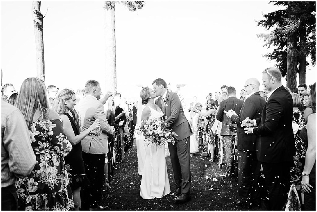 Black and white photo of bride and groom sharing a kiss while walking back down the aisle after exchanging vows, PNW outdoor summer wedding, Washington wedding designer, Perfectly Posh Events, Photo by Kate Price Photography
