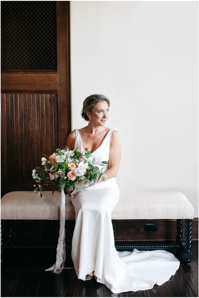 Bride wearing a white wedding gown sits on a indoor bench while holding a large bouquet made of white and pink flowers with greenery, PNW outdoor summer wedding, Washington wedding designer, Perfectly Posh Events, Photo by Kate Price Photography