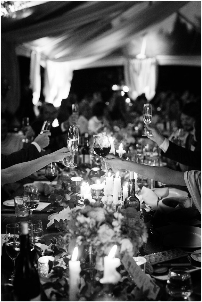 Black and white photo of wedding guests sharing a champagne toast at the dinner table during their wedding reception, PNW outdoor summer wedding, Washington wedding designer, Perfectly Posh Events, Photo by Kate Price Photography