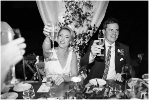 Black and white photo of bride and groom sharing a champagne toast with their guests at the dinner table during their wedding reception, PNW outdoor summer wedding, Washington wedding designer, Perfectly Posh Events, Photo by Kate Price Photography