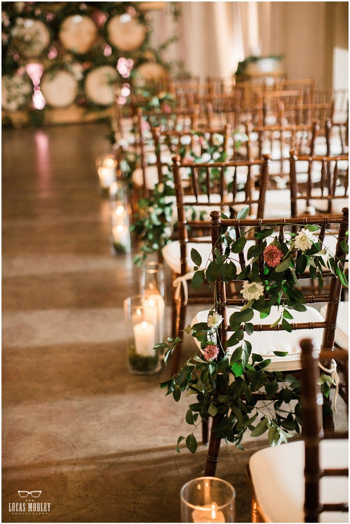 Close up of wood chairs set up for an indoor wedding ceremony decorated with greenery and ivory and pink flowers, The Foundry by Herban Feast wedding, fall wedding, Seattle wedding planner, Perfectly Posh Events, Photo by Lucas Mobley Photography