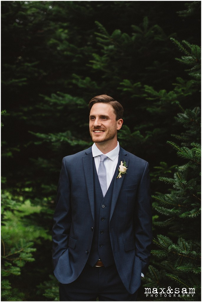 Groom in a navy suit with a blue tie poses in front of pine trees, The Lodge at Fall City wedding, Seattle wedding, planning and design by Perfectly Posh Events, Seattle Wedding Planner, Photo by Max & Sam Photography