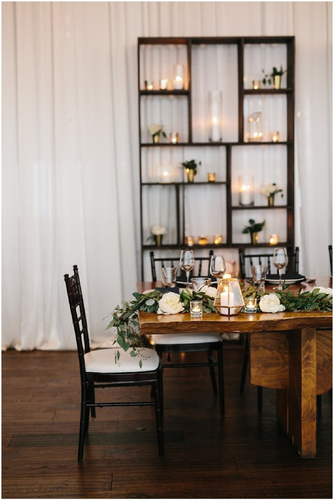 Rustic wood wedding reception dinner table decorated with greenery with a bookshelf covered in candles in the background, same sex wedding, Sodo Park wedding, Seattle wedding coordinator, Perfectly Posh Events, Photo by Melissa Kilner Photography