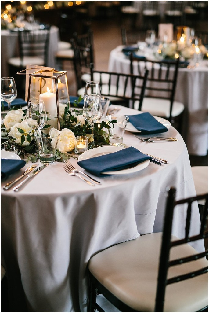 Wedding reception dinner table covered in a white tablecloth and navy napkins is decorated with candles, ivory flowers, and greenery, same sex wedding, Sodo Park wedding, Seattle wedding coordinator, Perfectly Posh Events, Photo by Melissa Kilner Photography