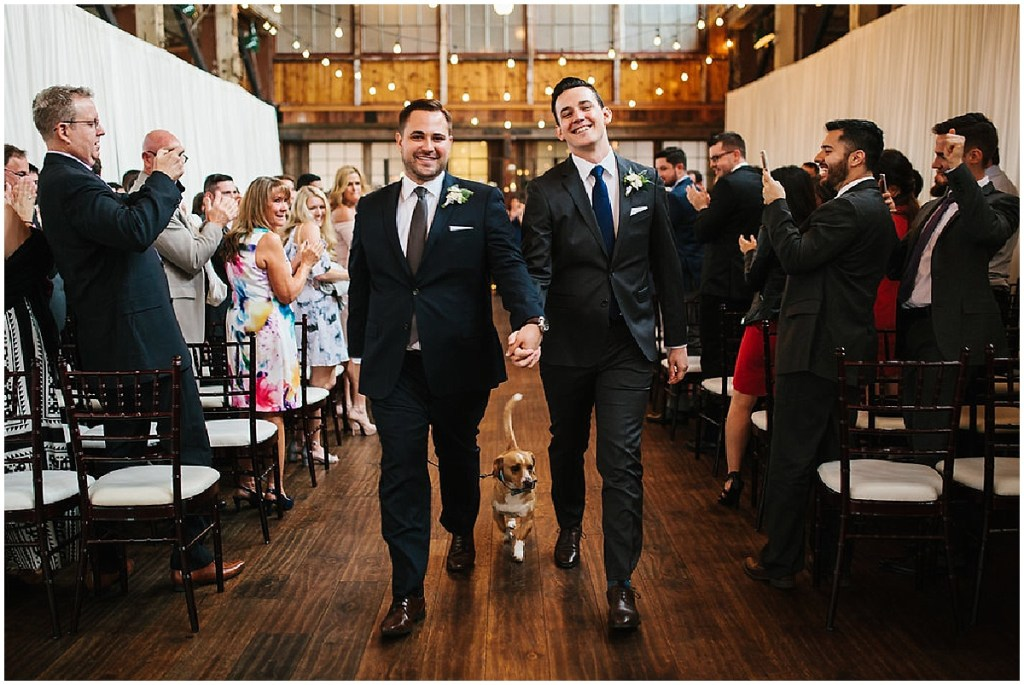 Newlywed grooms walk back down aisle with their dog after exchanging vows while their friends and family cheer them on, same sex wedding, Sodo Park wedding, Seattle wedding coordinator, Perfectly Posh Events, Photo by Melissa Kilner Photography